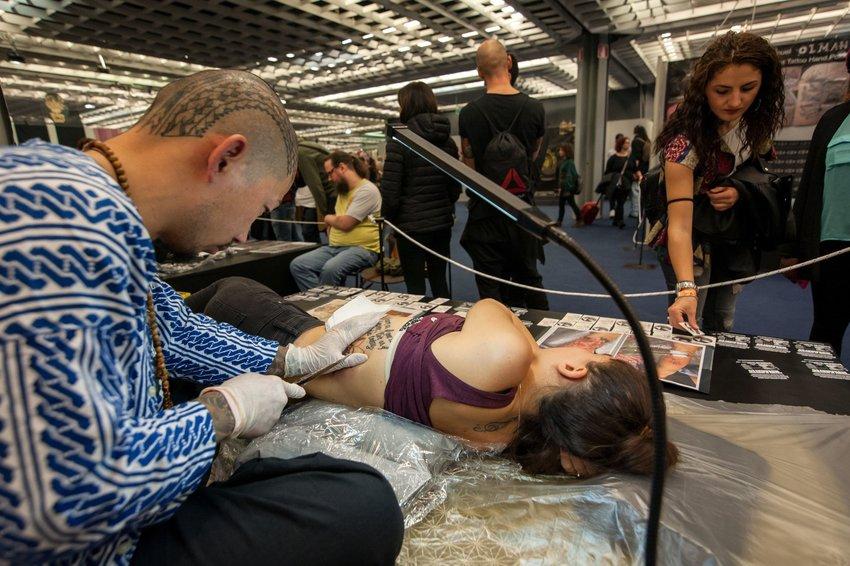 Woman getting a tattoo through a traditional Tebori technique