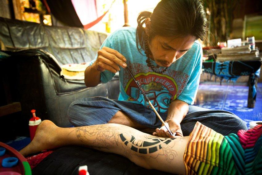 Expert artist giving a tourist a thai bamboo tattoo
