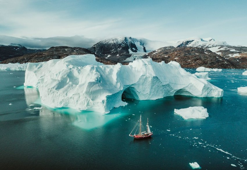 Aerial photo of ship next to iceberg in the water