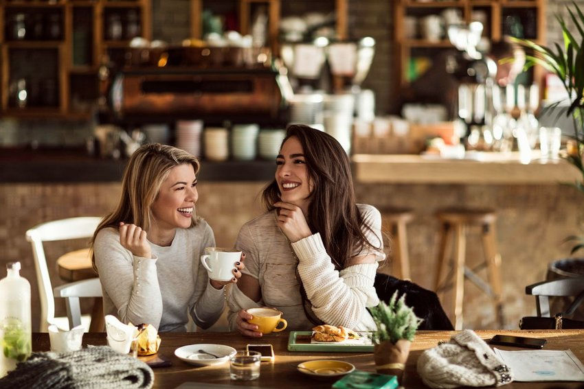 Two women having breakfast at a cafe with coffee cups in hands