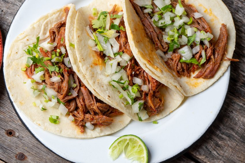 Three barbacoa tacos with cilantro, onion and lime in flower tortillas