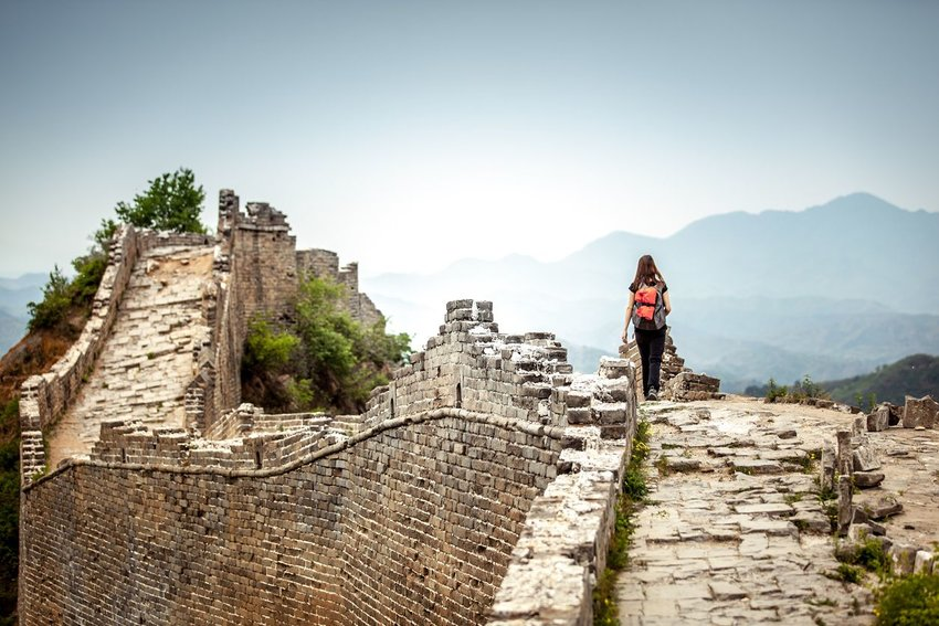 Woman walking along the Great Wall of China with a backpack on