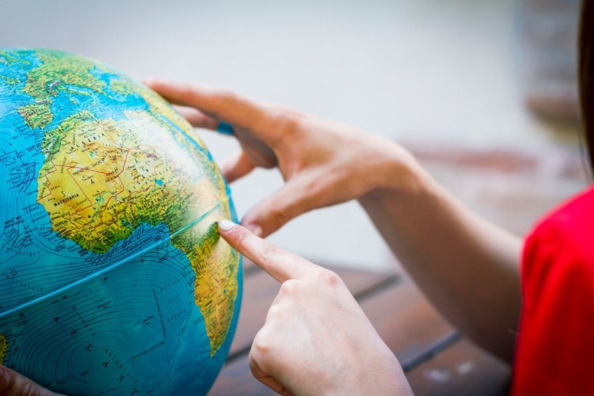 Person pointing at Africa on a world globe