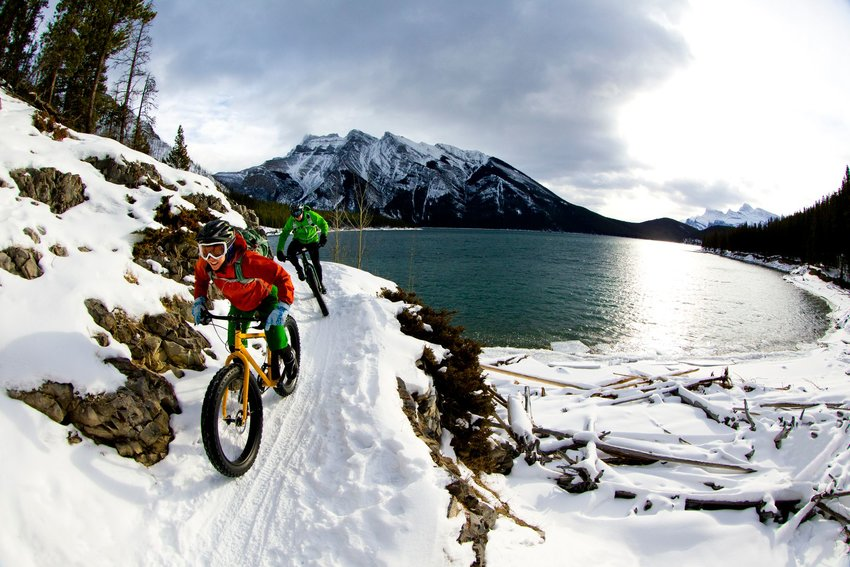 Two people snow biking next to a cold lake in Banff National Park, Alberta, Canada.