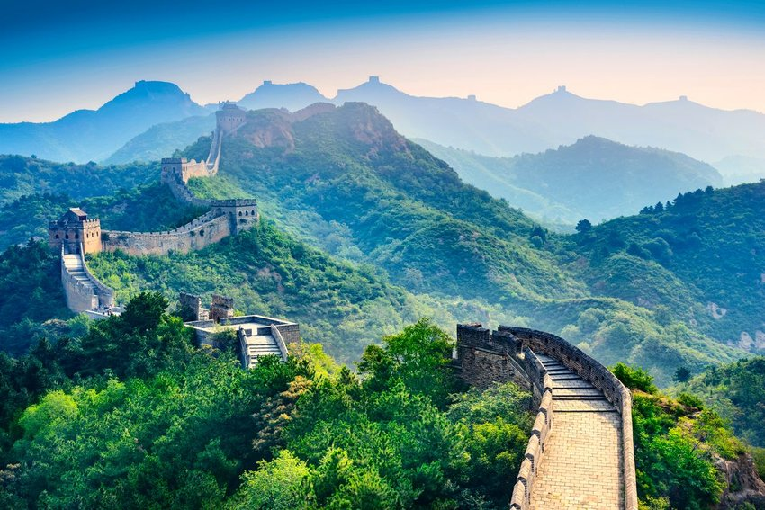 The Great Wall of China surrounded by lush green foliage