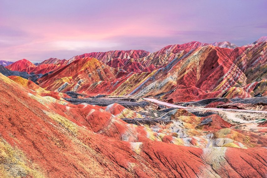 A pink and purple sunset at the incredibly colorful Rainbow Mountains in China