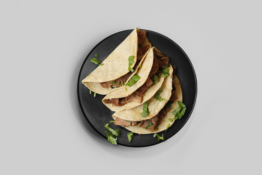 Three tacos on a black plate