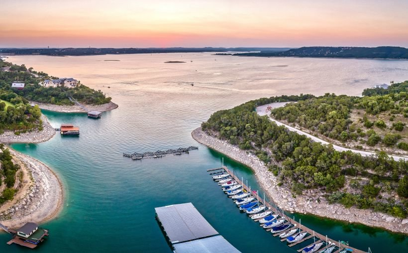 Lake Travis in Texas with boats lined up at a dock at sunset