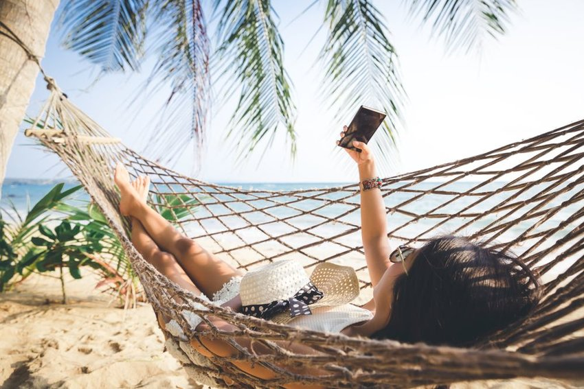 Woman lying in hammock on the beach while on the phone