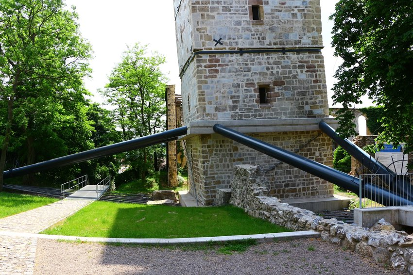 The leaning tower of Bad Frankenhausen, Germany, being held up by modern support beams.