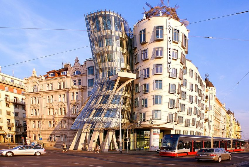 Street view at sunset with famous Dancing House and street traffic
