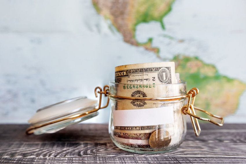 Money in a clear jar with a map in the background