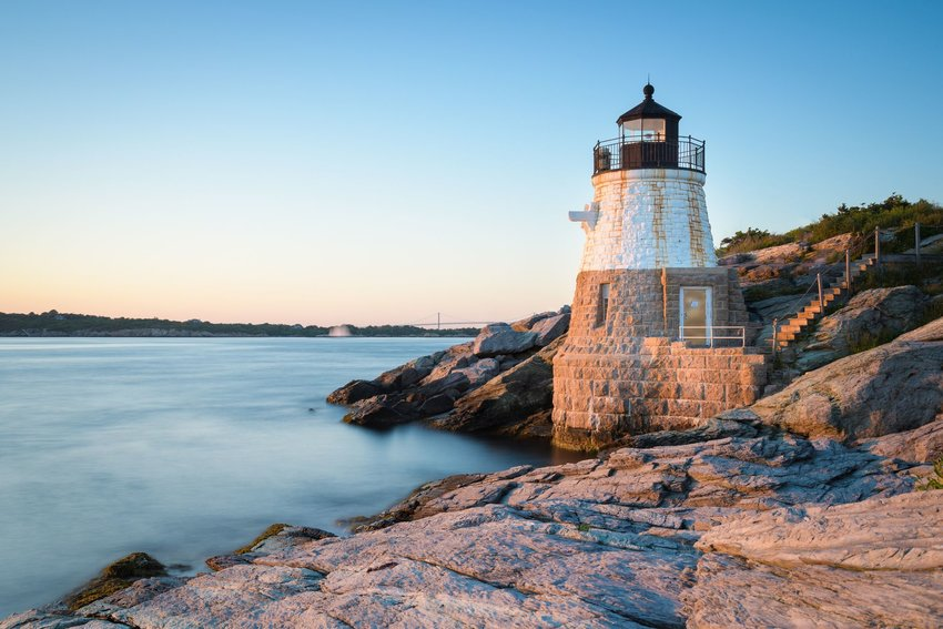 The sun is setting upon Castle Hill Lighthouse overlooking the bay in Newport, Rhode Island.