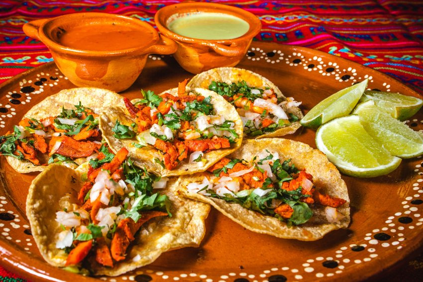 Five tacos al pastor with salted limes and salsas ready for consumption