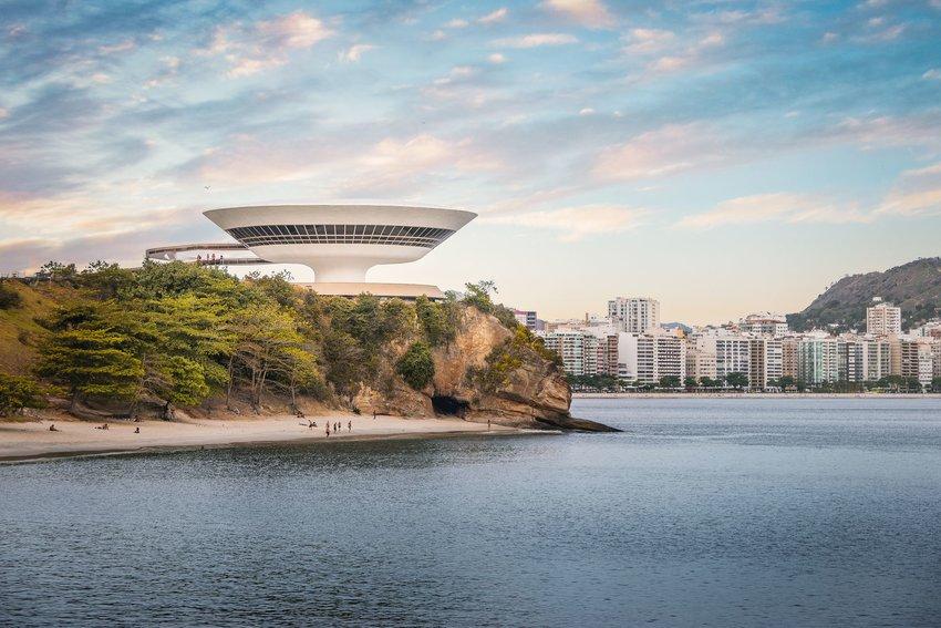 Niterói Museum of Contemporary Art on the edge of a cliff with Rio Janeiro behind it