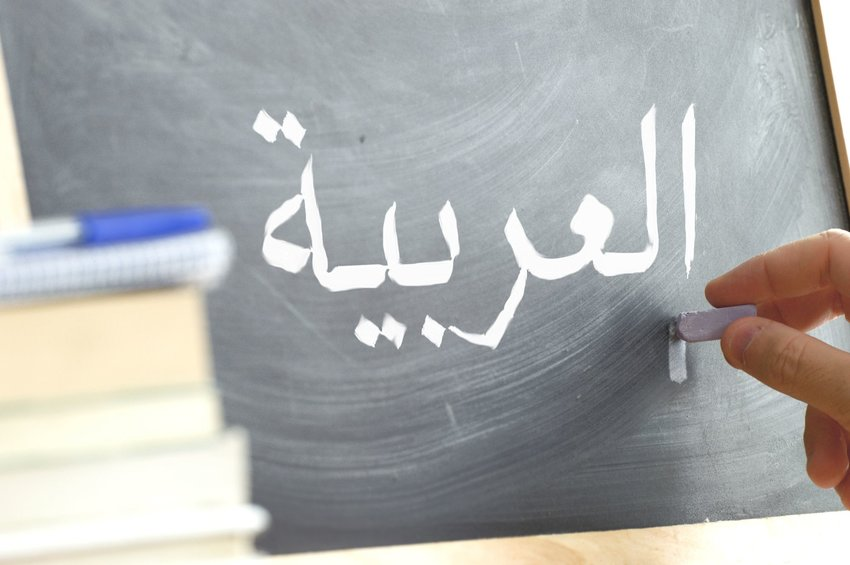 "Hand writing ""Arabic"" on a chalkboard"