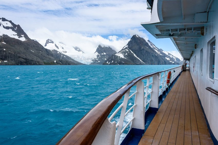 Side of cruise in the water with snowy mountains in the background