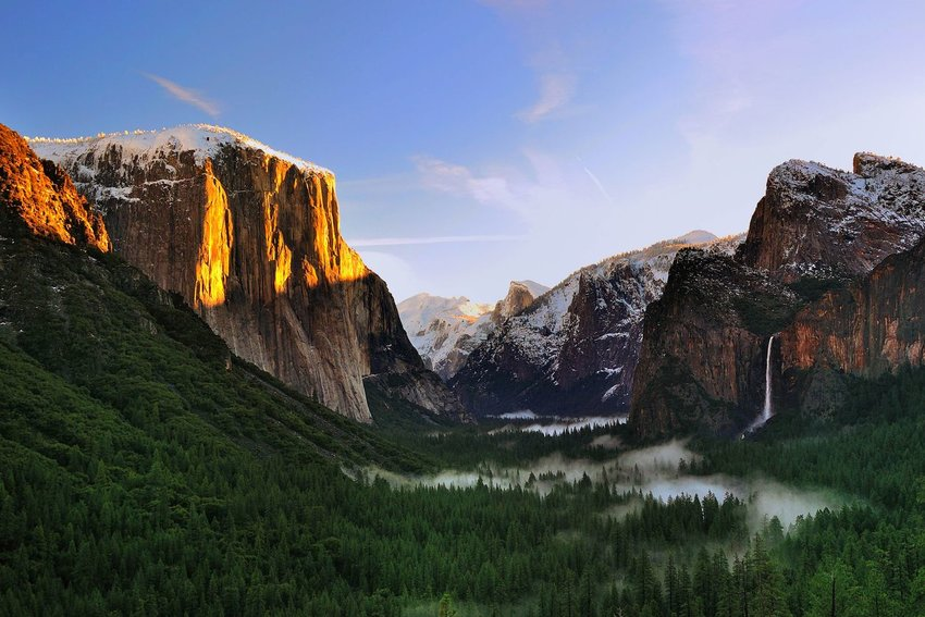 Sunrise hitting peaks in Yosemite National Park with fog through the forest below