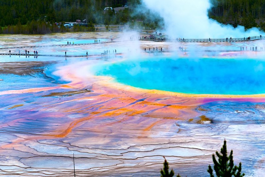 Colorful geyser with people walking on bridge behind in Yellowstone National Park