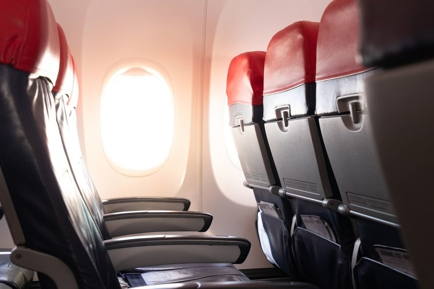 Interior of airplane with view of row of seats and open window