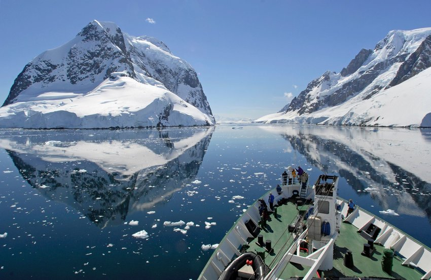 A small cruise ship makes passage through the Lemaire Channel in Antarctica