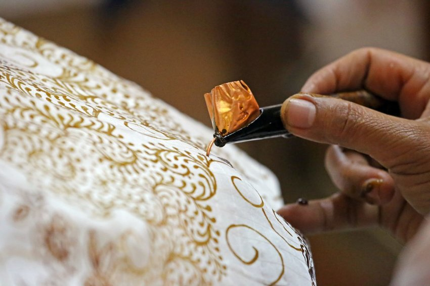 A woman uses a canting to apply wax to a cloth to make a pattern on a batik