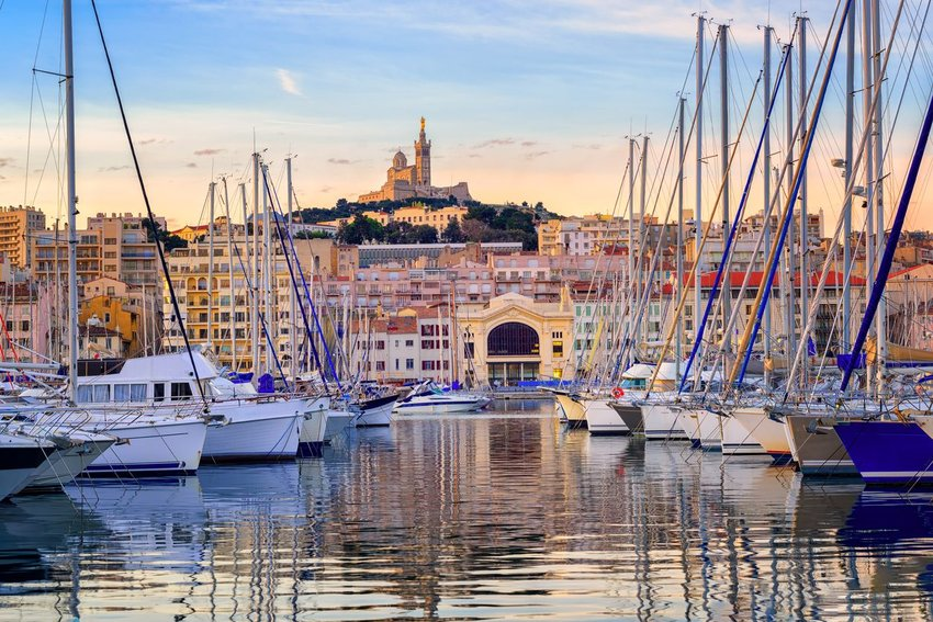 Yachts reflecting in the still water of the old Vieux Port of Marseilles beneath Cathedral of Notre Dame, France, at sunrise