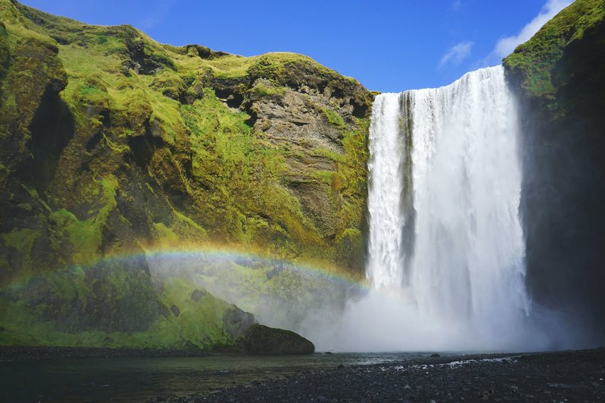 Skógafoss waterfall shot from below with a rainbow in Iceland