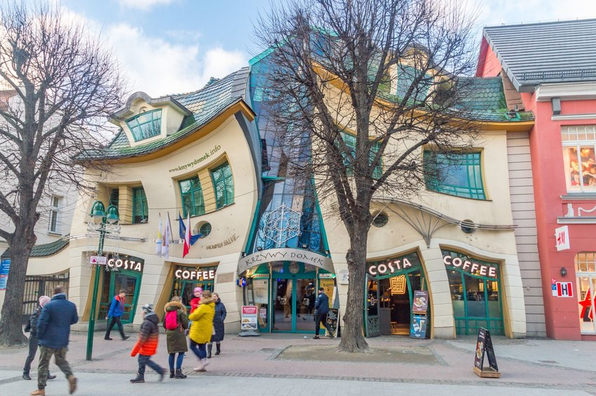 Crooked building with shoppers out front in Poland