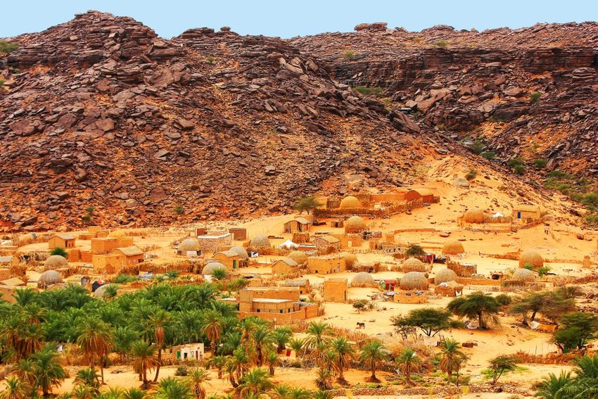 Village at the bottom of hills with palm trees in Mauritania, Africa