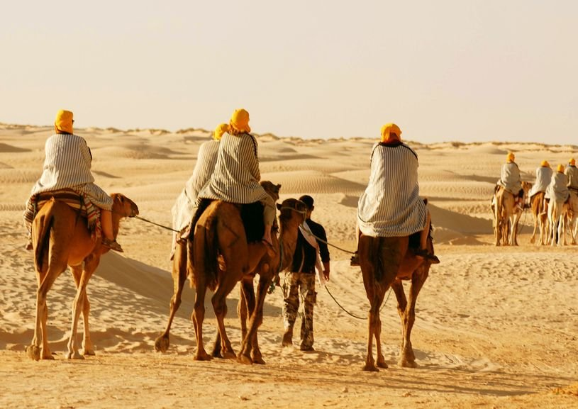 People ride on camels with a guide in the Sahara right outside of Douz, Tunisia