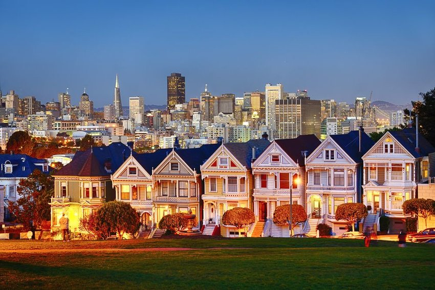 The Painted Ladies of San Francisco, California sit glowing amid the backdrop of a sunset and skyscrapers