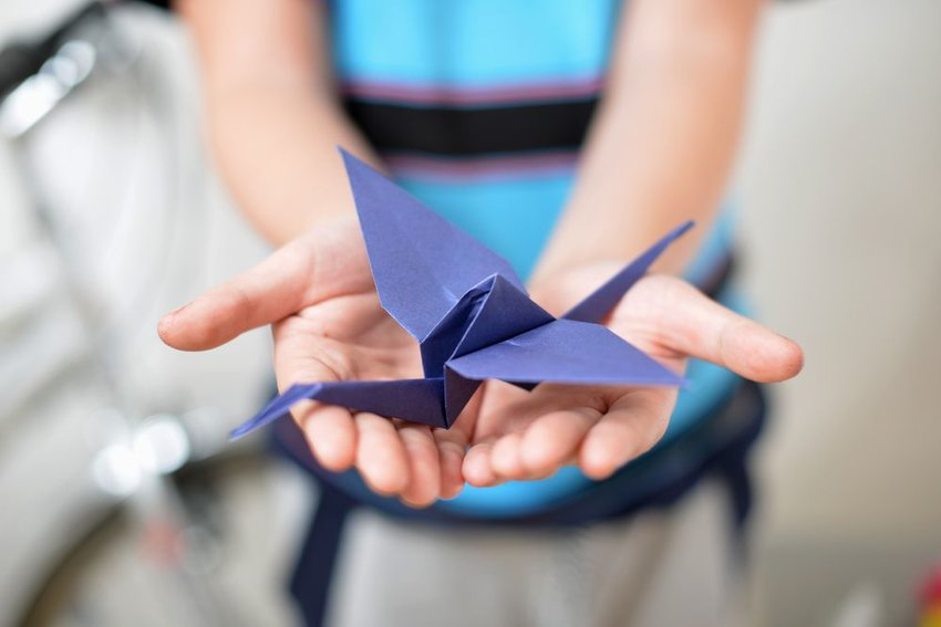 Purple origami crane in children's hands