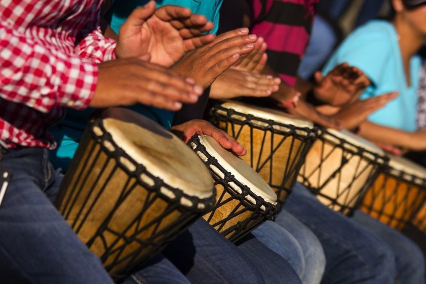 Group of people playing djembe African drums