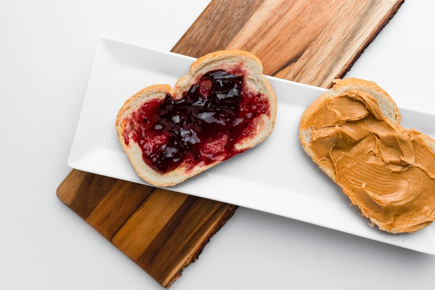 Peanut butter and jelly sandwich laying open on a white plate and a wooden slab