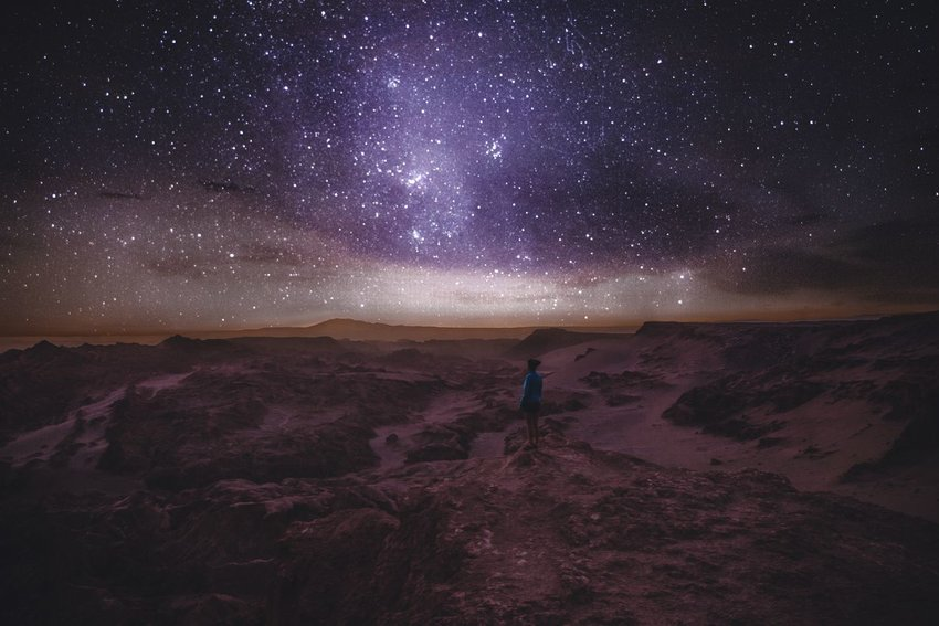Woman standing in Atacama Desert with stars above
