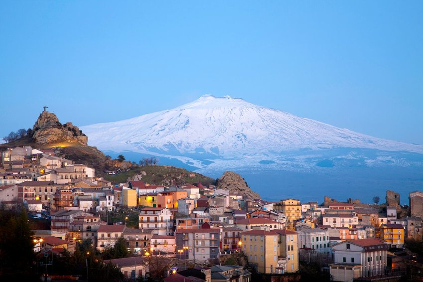 View of the village of San Teodoro and Etna volcano on background in Sicily