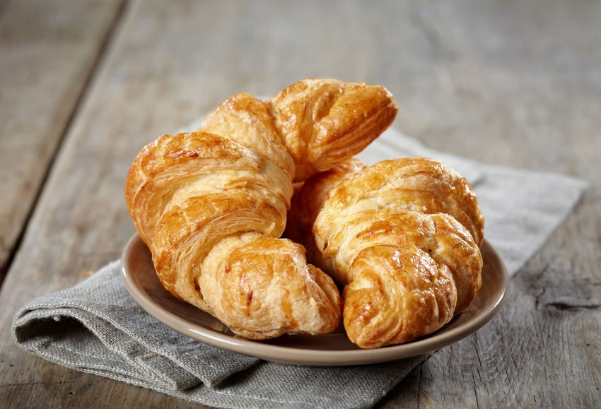 Two croissants on a plate with a cloth napkin