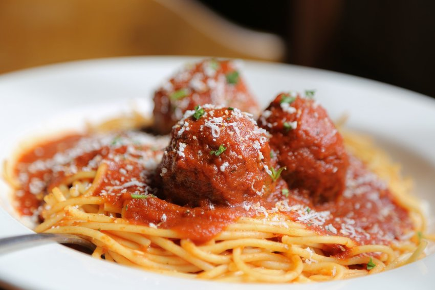Spaghetti and meatballs in a white bowl with a fork