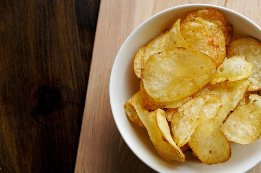 Bowl of potato chips on a wooden table