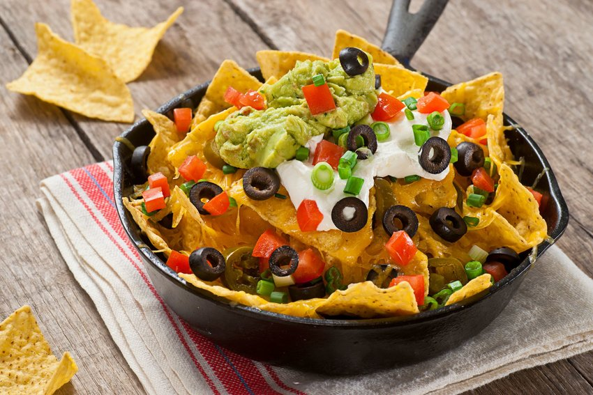 Tortilla chips covered in guacamole, olives and tomatoes