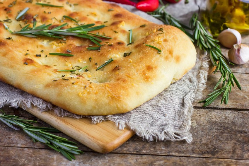 Italian focaccia bread with rosemary and garlic on a rustic background