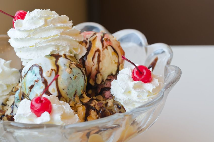 Ice cream sundae in clear bowl with whipped cream and cherries on top