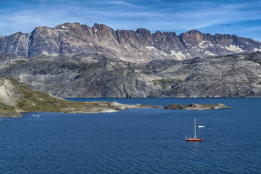 Boat in the water on the edge of rocky cliffs of Greenland