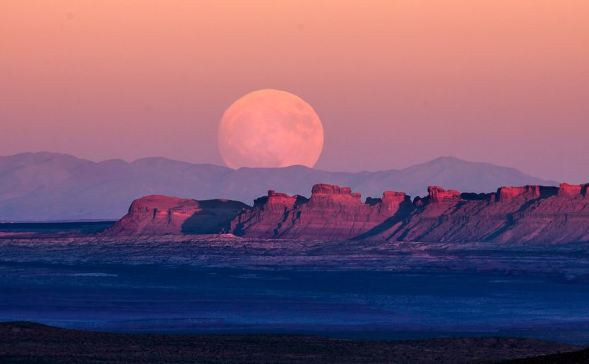 A giant full moon rising over the desert and plateaus of Monument Valley