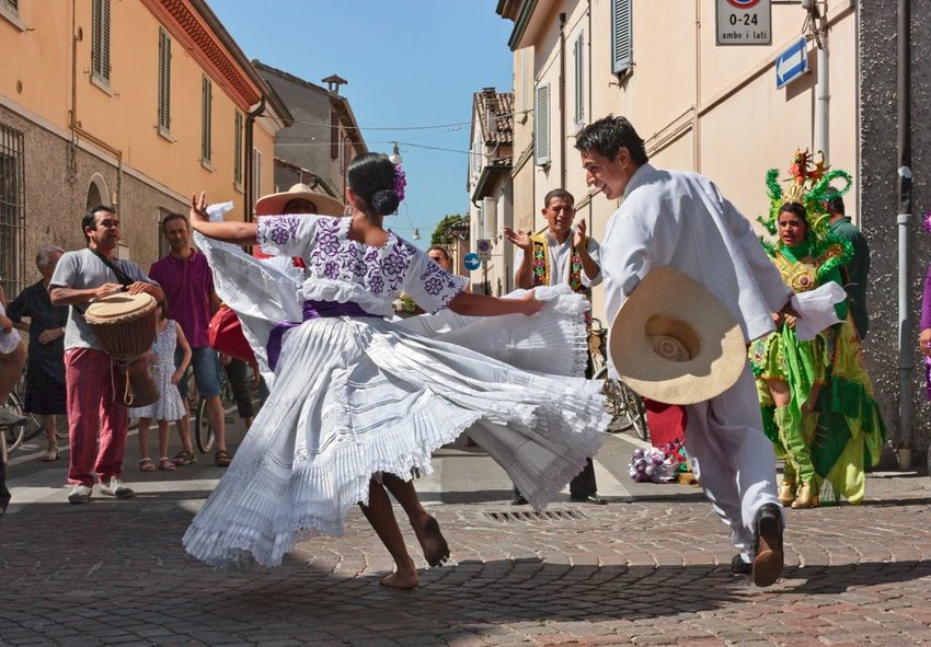 "Two dancers in all white dance ""La marinera"" at International folk festival"
