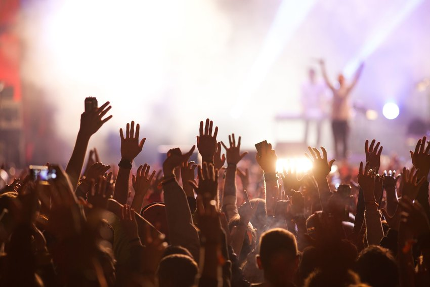 Crowd of people with their arms in the air at a concert