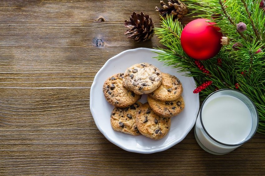 Cookies and milk with Christmas ornament on wooden table