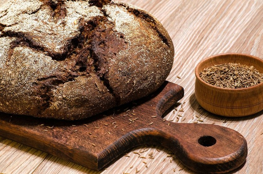 Dark rye loaf of bread on a wooden cutting board and seasoning on the side