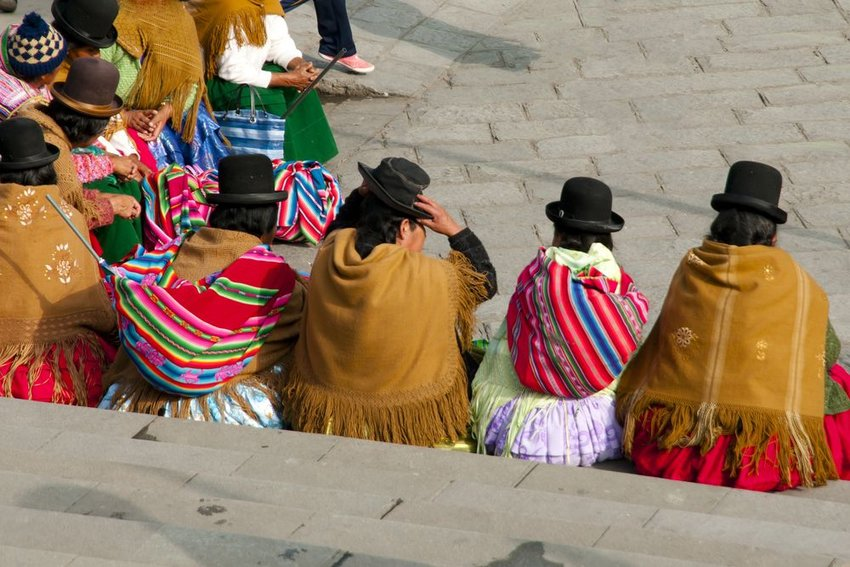 Cholitas wearing bowler hats sitting on steps